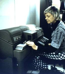 NWS employee at a teletype machine with paper tape reader, circa 1970s