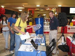 Meteorological Intern Robert Hart discussing the 2009 edition of Skywatcher chart with a visitor, La Plaza Mall Hurricane Expo, McAllen