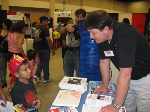 Photo of Forecaster Ryan Vipond talking weather safety with a youngster at the Hidalgo County Dare to Prepare Readiness Expo, July 11, 2009 (Click for larger image)