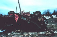 Tornado crushes and rolls farm vehicle, pinning it against a post.