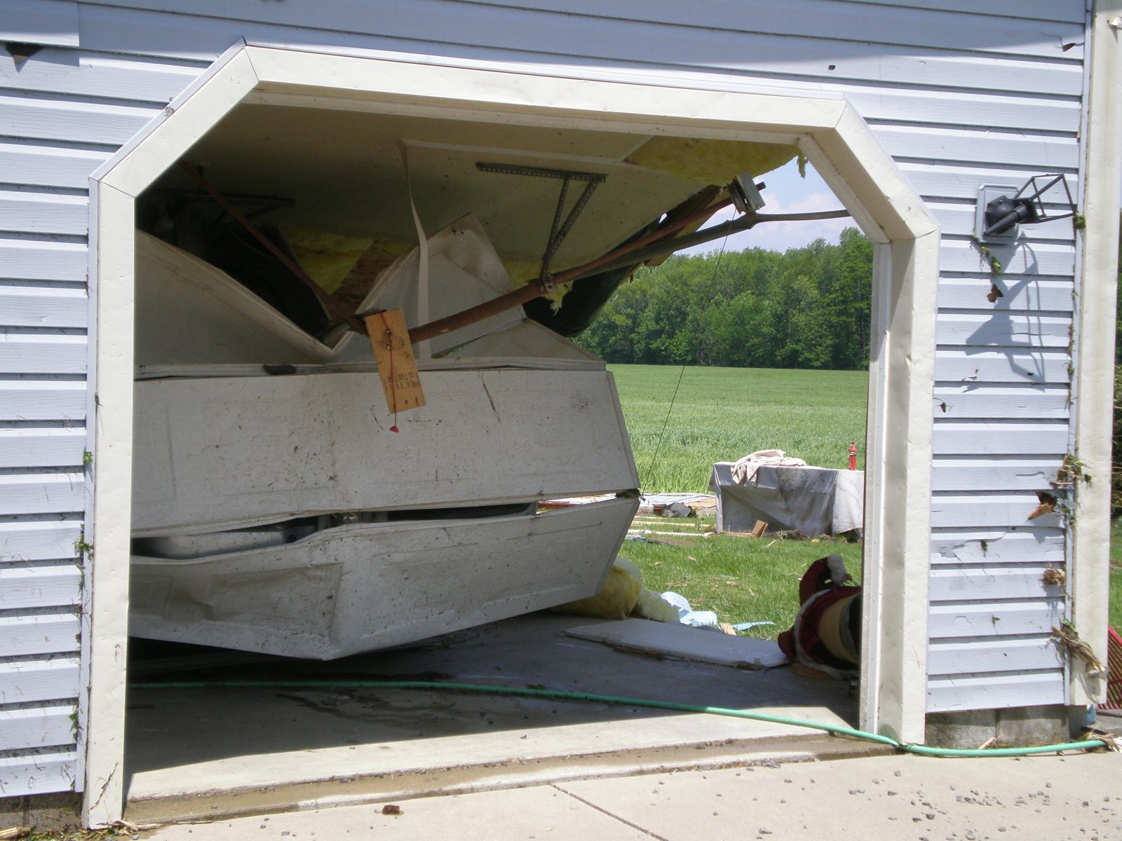 garage door blown in with side garage wall missing