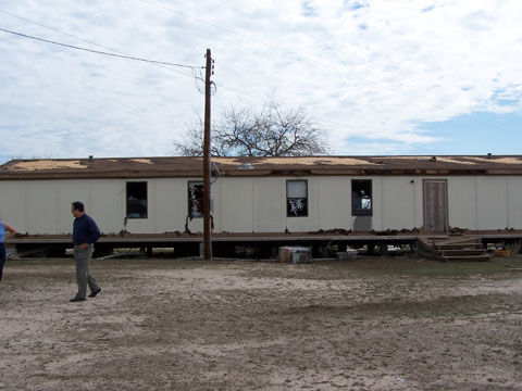 Windows broken and shingles missing from NW side of mobile home