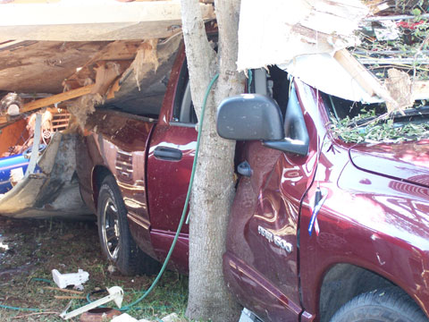 Mobile home pushed truck up against tree