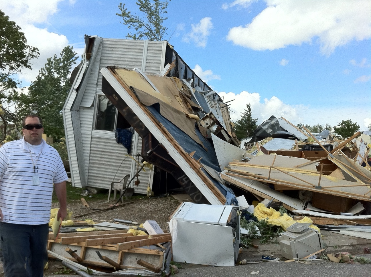Meteorologist Chris Bowman standing by damaged mobile home