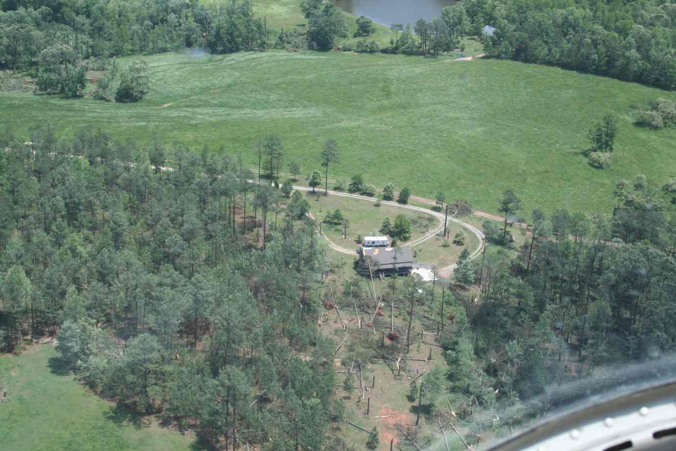 [ Aerial view of damage to home and tornado's path through wooded area. ]
