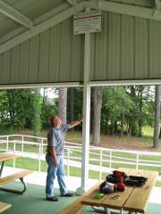 [ Rick Ullom, Hydrologist, Southeast River Forecast Center, looks at a high water mark sign installed at Legion Park. ]