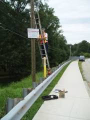 [Kent Frantz, Service Hydrologist, Weather Forecast Office Peachtree City, installs a high water mark sign by the Powders Springs Road bridge. ]