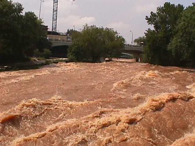 The Reedy River surges through the west end of downtown Greenville, South Carolina, on 29 July 2004