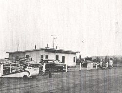 Facing north-northeast toward the Huntsville Municipal Airport Administration Building on May 13, 1946.  The instrument shelter can be seen on the right side of this picture, on the northeast side ofhte building.  Wind vane and anemometer are on top of the building.