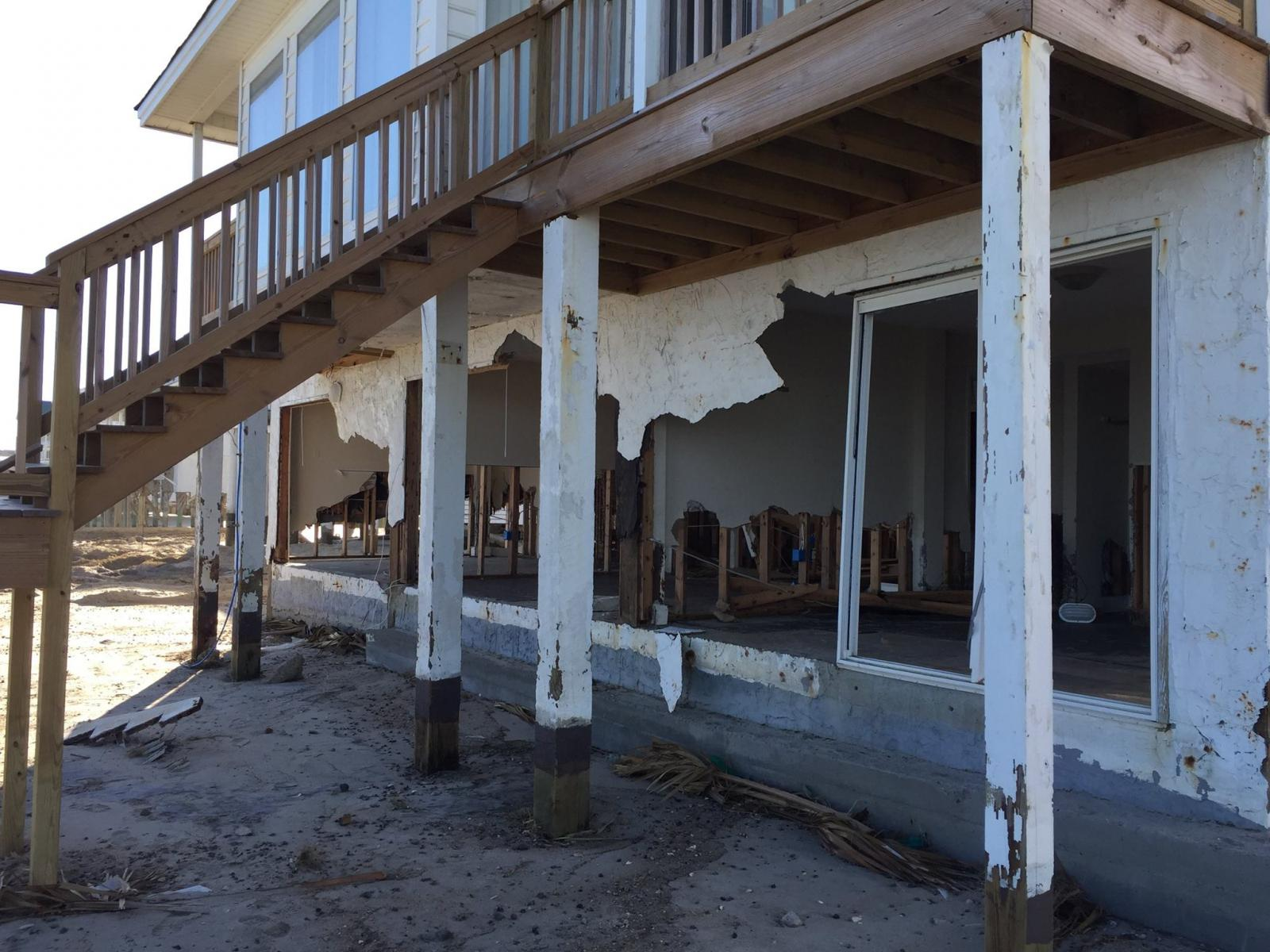 Hurricane Matthew's storm surge heavily damaged the first floor of this home on South Waccamaw Drive in Murrells Inlet, SC, and caused significant beach erosion.  Note how much sand was eroded from around the posts supporting the balcony and stairs.