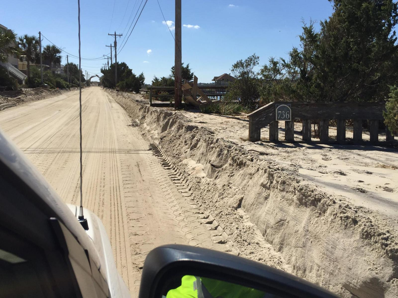 Deep sand covers the Springs Road in Pawleys Island, SC, carried in by Hurricane Matthew's storm surge.