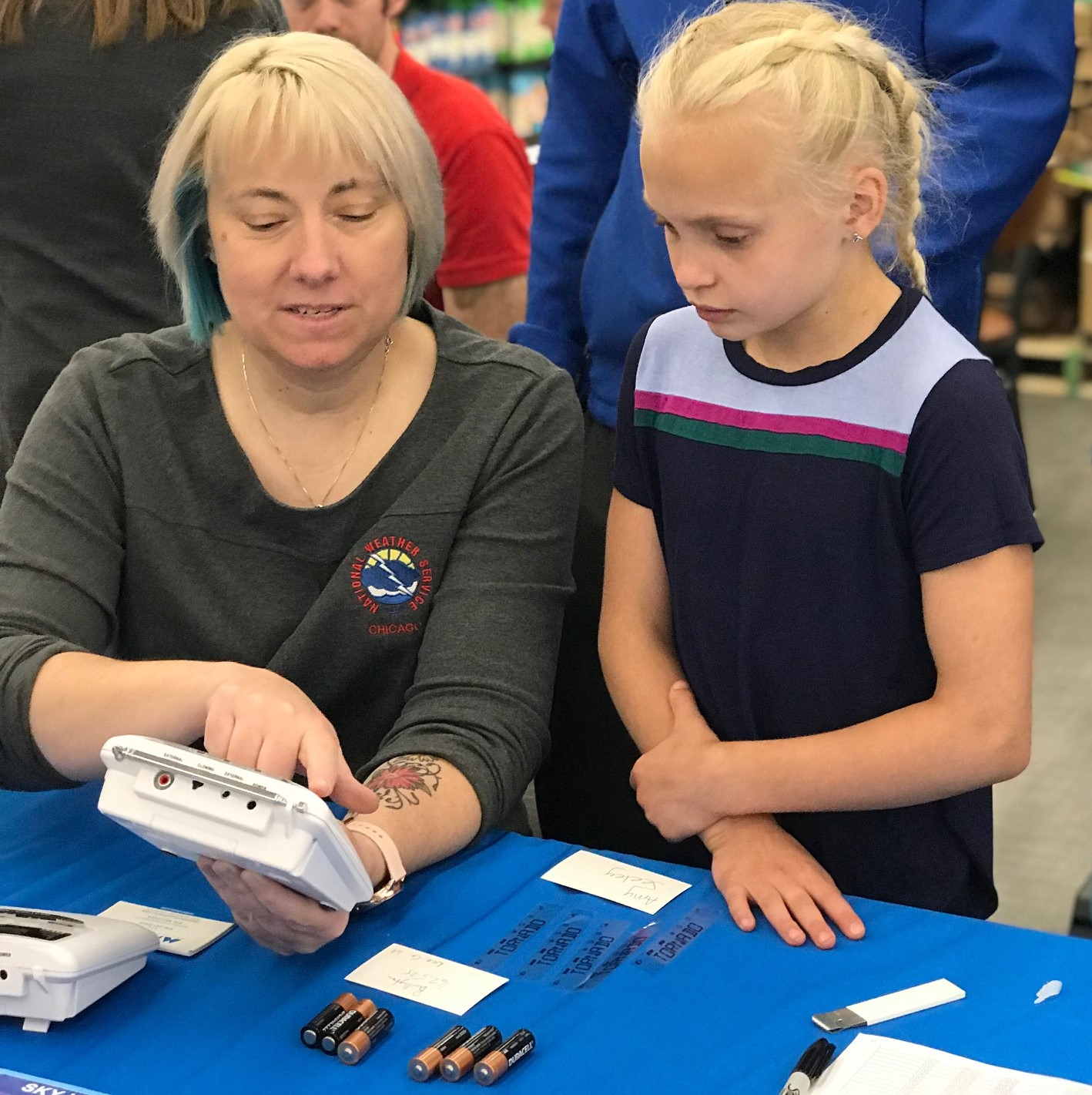 Amy teaching a child about a weather radio