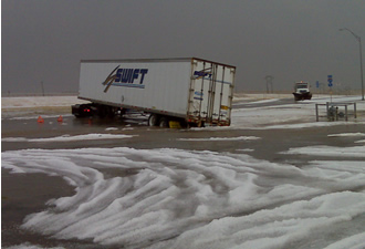 A tractor-trailer stuck in the flowing water and hail at a truck stop in Tulia