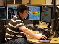 Forecaster working at an AWIPS workstation.