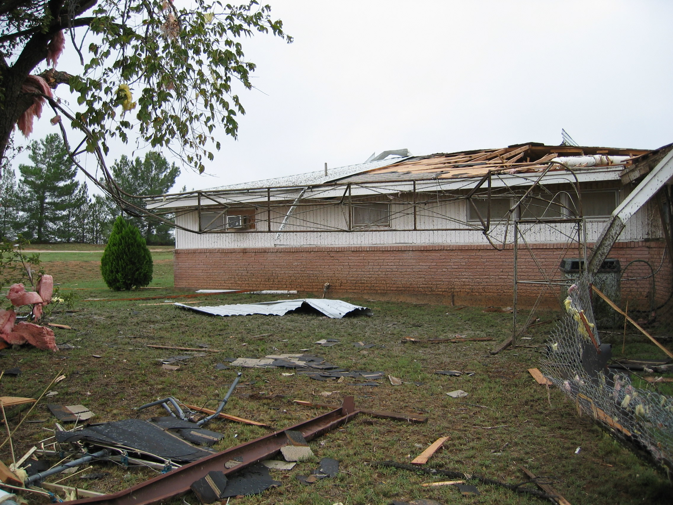 Photo of house with damaged roof, caused by an F1 tornado.