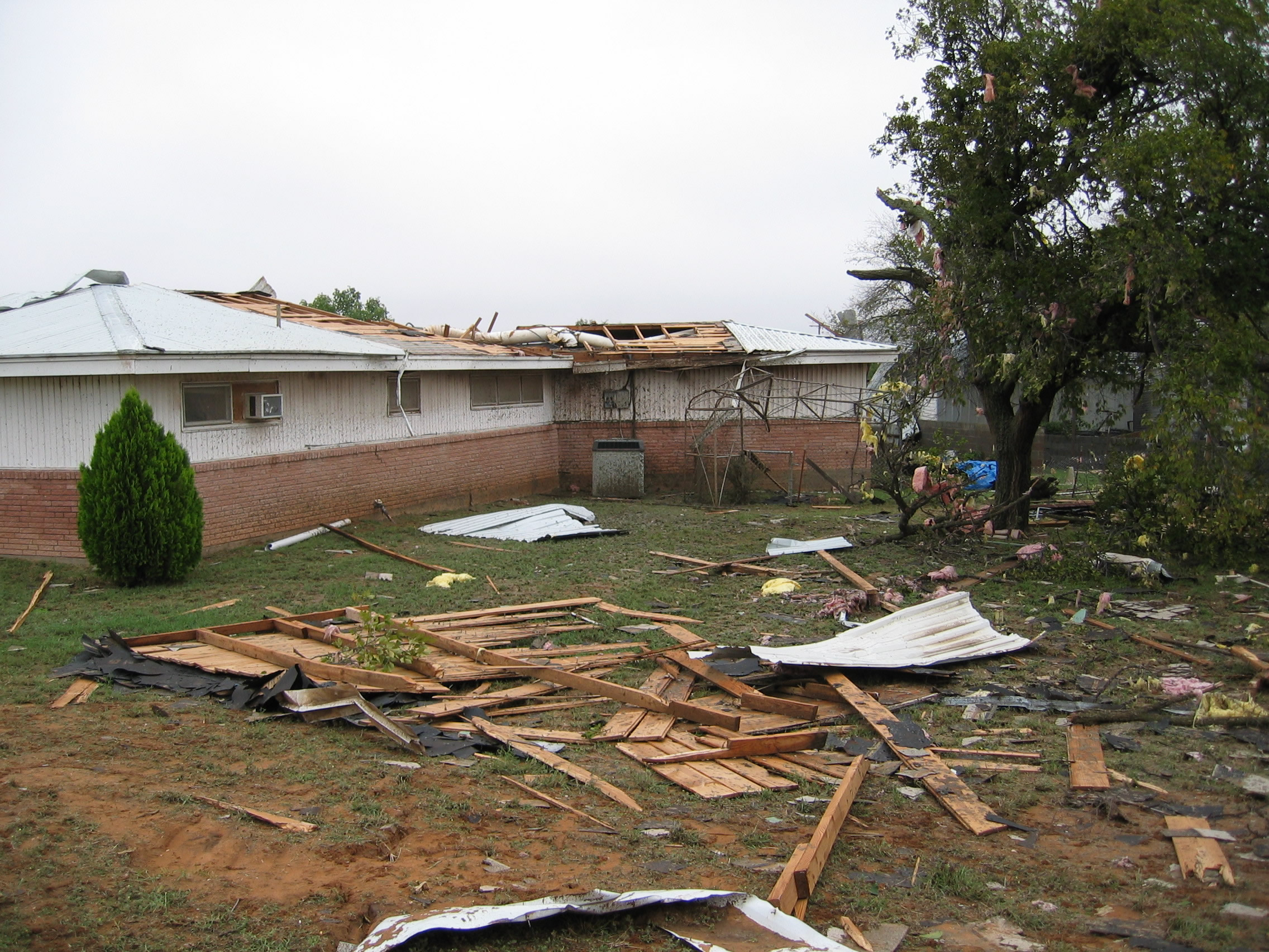 Second photo of house sustaining F1 tornado damage showing roof blown from the house.