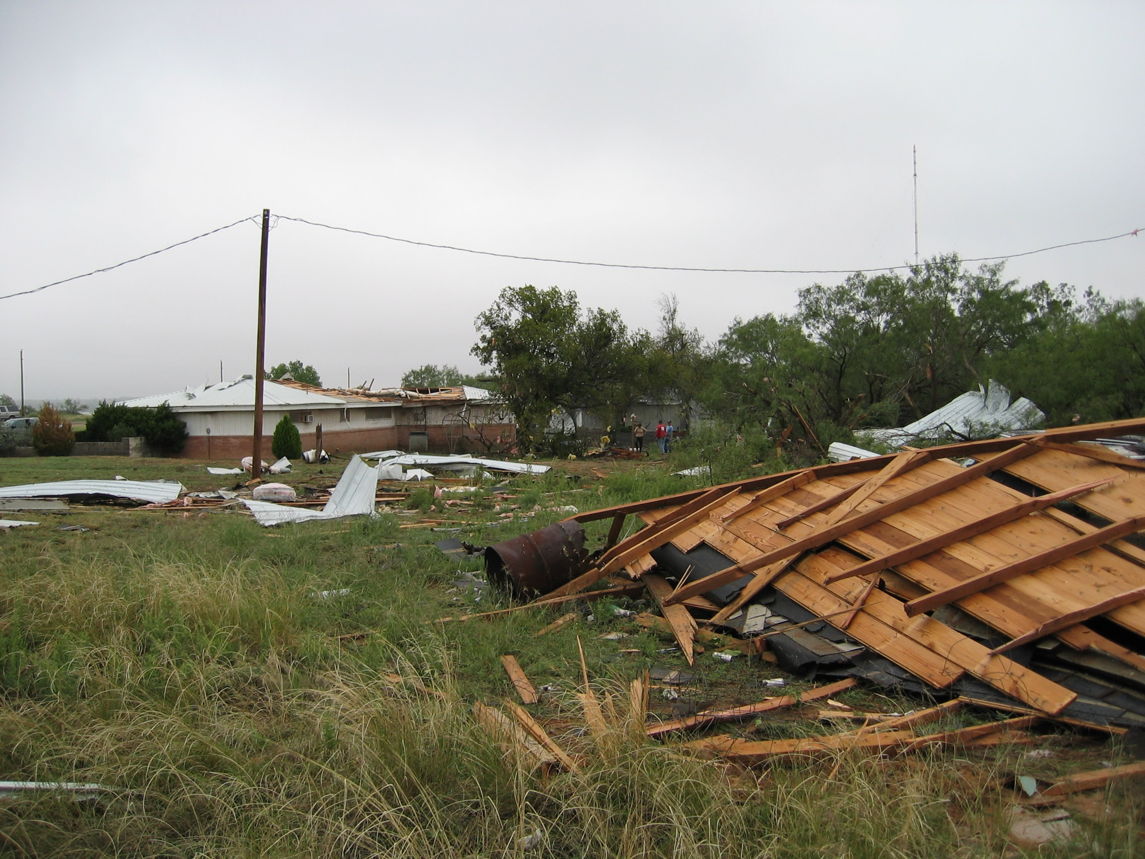 Third photo of house sustaining F1 tornado damage showing more roof blown a significant distance.""