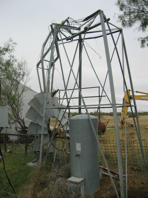 Photo of a bent wind mill near a residence along State Highway 137.