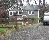 Photograph of the Sudbury River flooding a house on Stonebridge Road in Wayland, MA