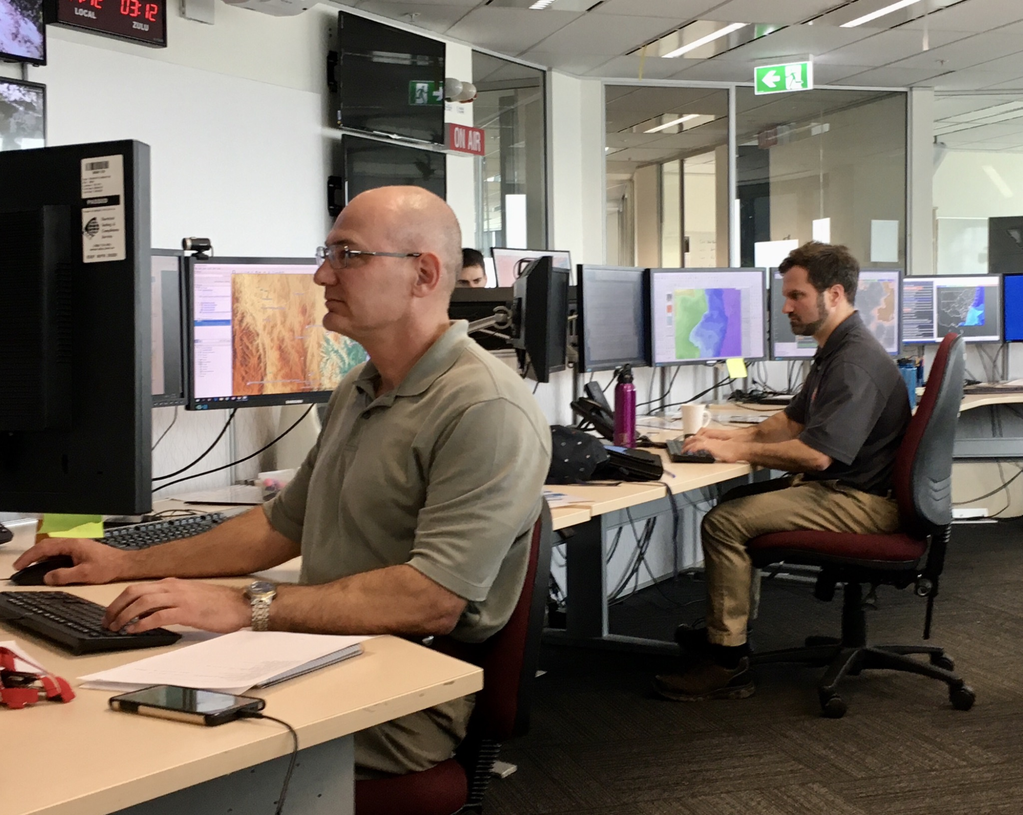 On right, IMET Mark Petterito (NWS Binghamton, NY) develops one of 20 spot weather forecasts requested by firefighters on this day. He works alongside meteorologists at the Australian Bureau of Meteorology regional office in Sydney. January 2020 Credit: NOAA