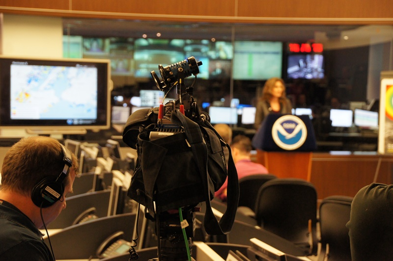 Image of media setting up for a news conference at a NOAA facility