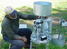 Picture of a technician performing maintenance on a rain gage - click to enlarge