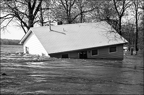 Floodwaters from the Mississippi River sweep away a house near Davenport, Iowa in April 1965. Photo by the Quad City Times.