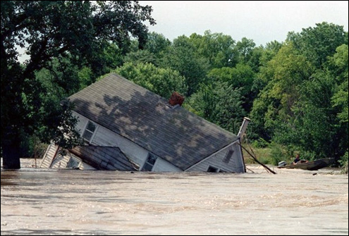 A 2-story house across the Iowa River from Wapello, Iowa was knocked off its foundation after a levee broke in early July 1993. Photo by the Des Moines Register.