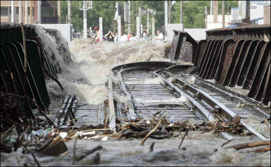 A railroad bridge is partially swept away by Cedar River floodwaters in downtown Waterloo, Iowa on June 10, 2008 as some people on the opposite river bank look on. Photo by The Waterloo Courier.