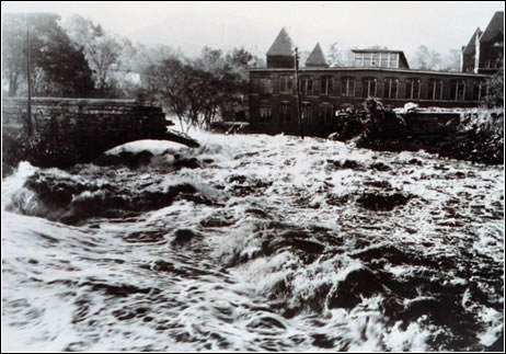Rapid floodwaters from the Swift River in Ware, MA, destroy a stone bridge and flood buildings. (NOAA)