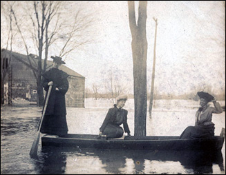 Residents in old time dress paddling boats down a flooded town street. Credit: State Archives