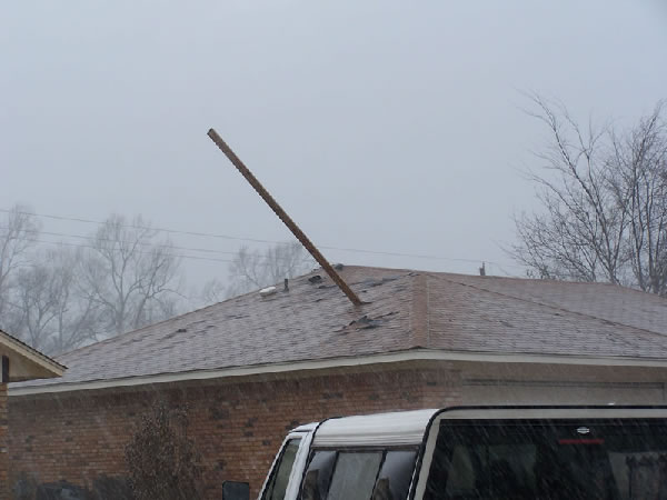 Wooden board blown into the roof of a home