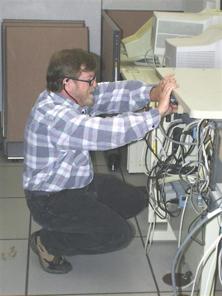 A picture of one of our HMTs connecting cables to one of our computers.