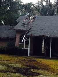 Roof damage sustained by a tree felled by gusty winds in Tallahassee, FL on Trescott Drive in Tallahassee, FL on December 24, 2015.